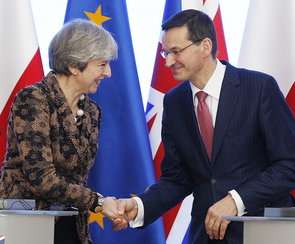 Polish Prime Minister Mateusz Morawiecki, right, and Britain's Prime Minister Theresa May shake hands during a press conference after signing a treaty...