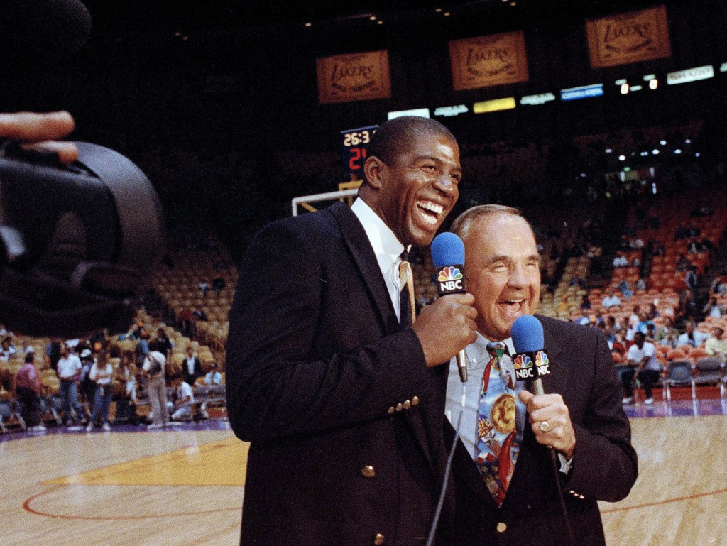 """FILE - In this Feb. 2, 1992, file photo, Earvin """"Magic"""" Johnson, left, and veteran sportscaster Dick Enberg laugh during commentary before the Los Ang..."""