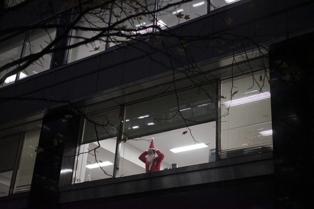 In this Dec. 22, 2017, file photo, a man prepares his Santa Claus outfit at the Marunouchi district office building in Tokyo. About 200 workers from t...
