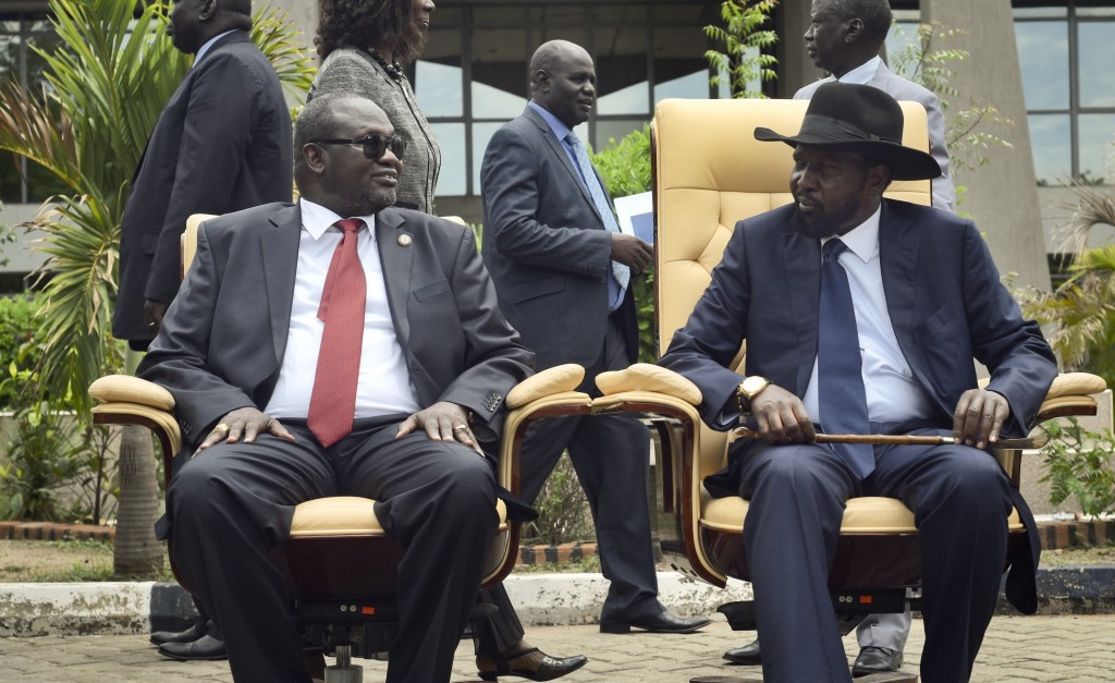 FILE - In this Friday, April 29, 2016 file photo, the then South Sudan's First Vice President Riek Machar, left, looks across at President Salva Kiir,...
