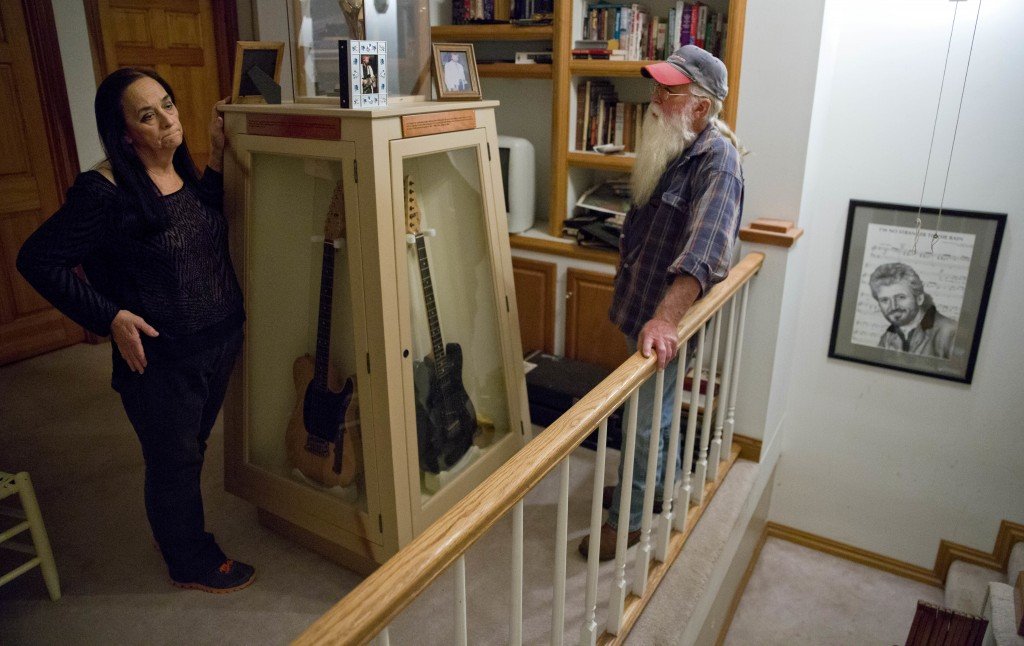 Flo and Dwight Whitley stand next to guitars belonging to Dwight's late brother, county and bluegrass musician Keith Whitley, as his portrait hangs in...