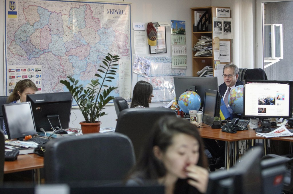 Kyiv Post chief editor Brian Bonner, right, and other journalists work at their desks in Kiev, Ukraine, on Friday, Dec. 8, 2017. Bonner and several ot...