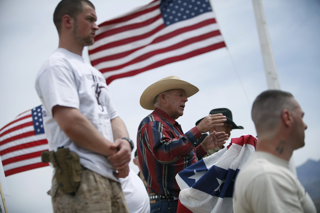 FILE - In this April 18, 2014, file photo, flanked by armed supporters, rancher Cliven Bundy speaks at a protest camp near Bunkerville, Nev. A U.S. ju...