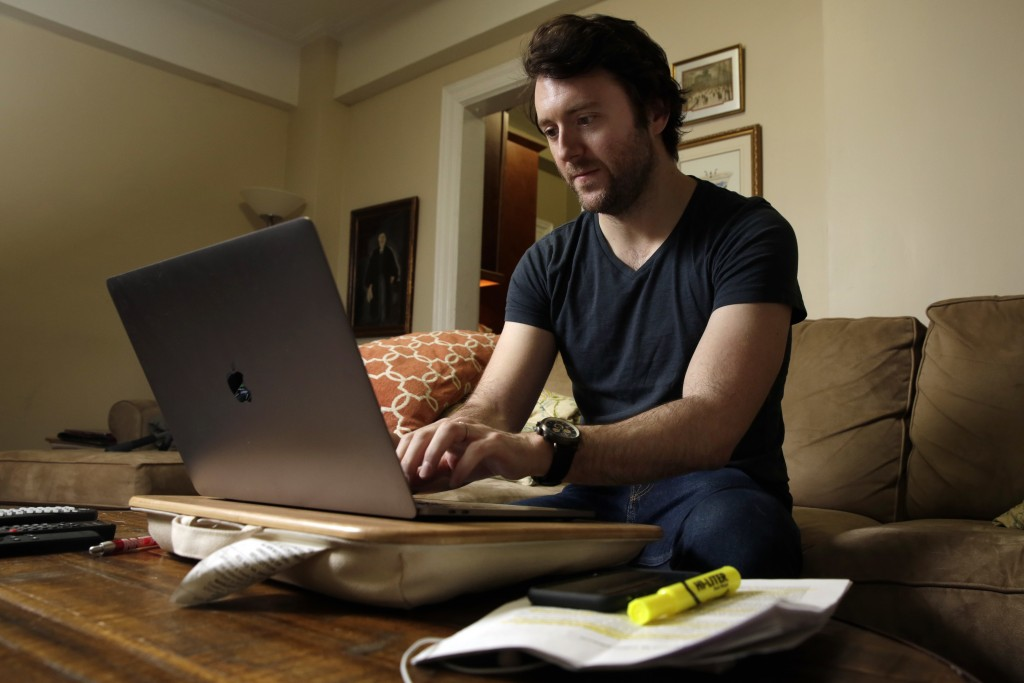 Journalist Michael Weiss works on his laptop in his apartment on New York's Upper West Side, Friday, Dec. 8, 2017. Weiss is one of at least 200 journa...