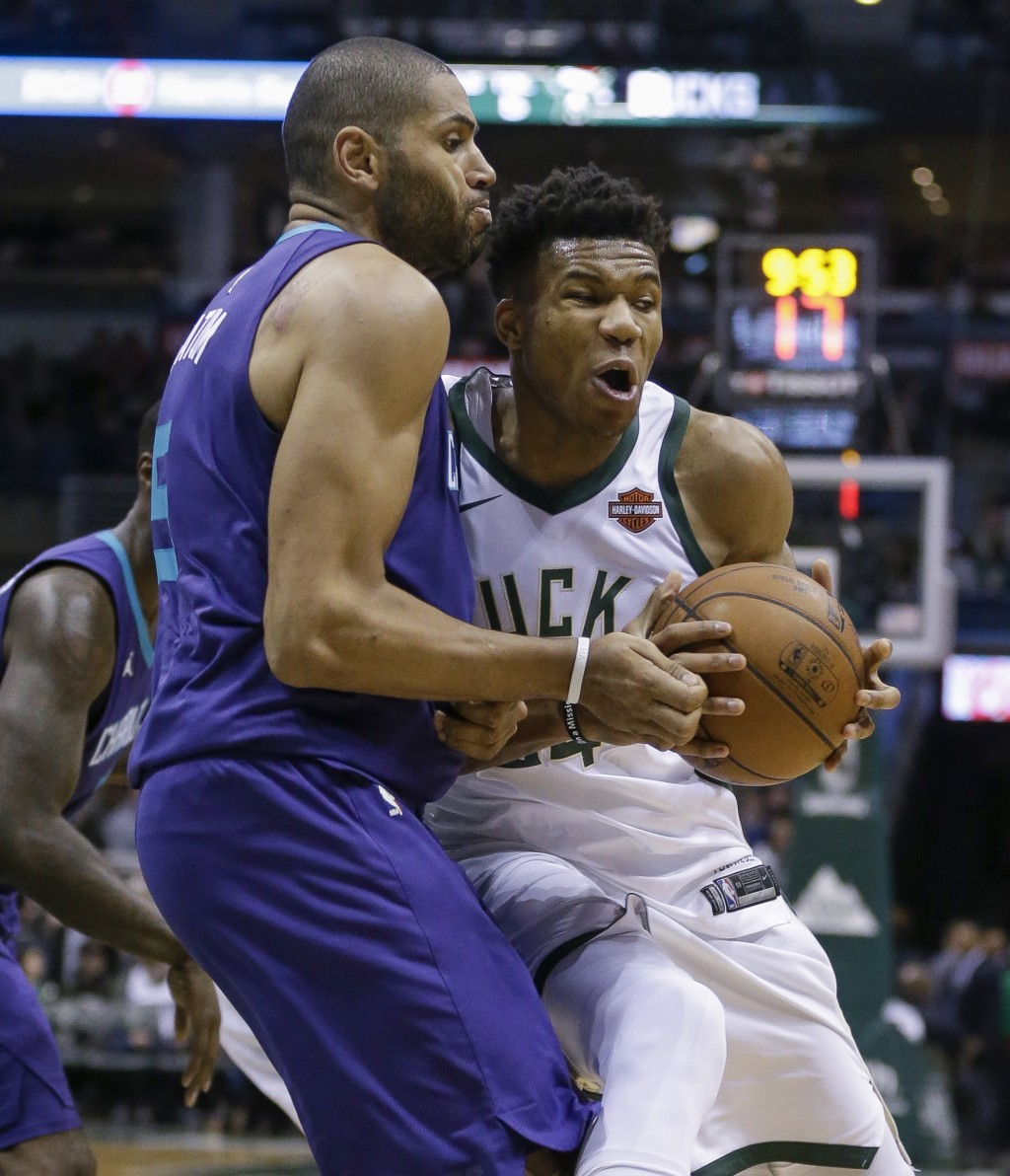 Milwaukee Bucks' Giannis Antetokounmpo runs into Charlotte Hornets' Nicolas Batum, left, while driving to the basket during the second half of an NBA ...