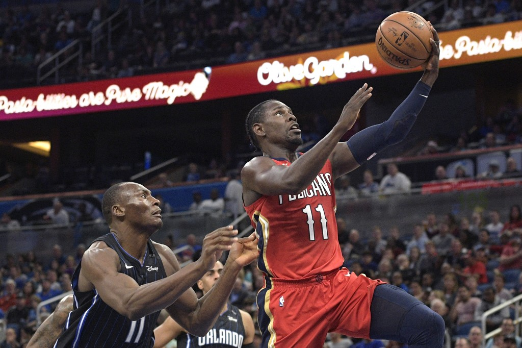 New Orleans Pelicans guard Jrue Holiday shoots in front of Orlando Magic center Bismack Biyombo, left, during the second half of an NBA basketball gam...