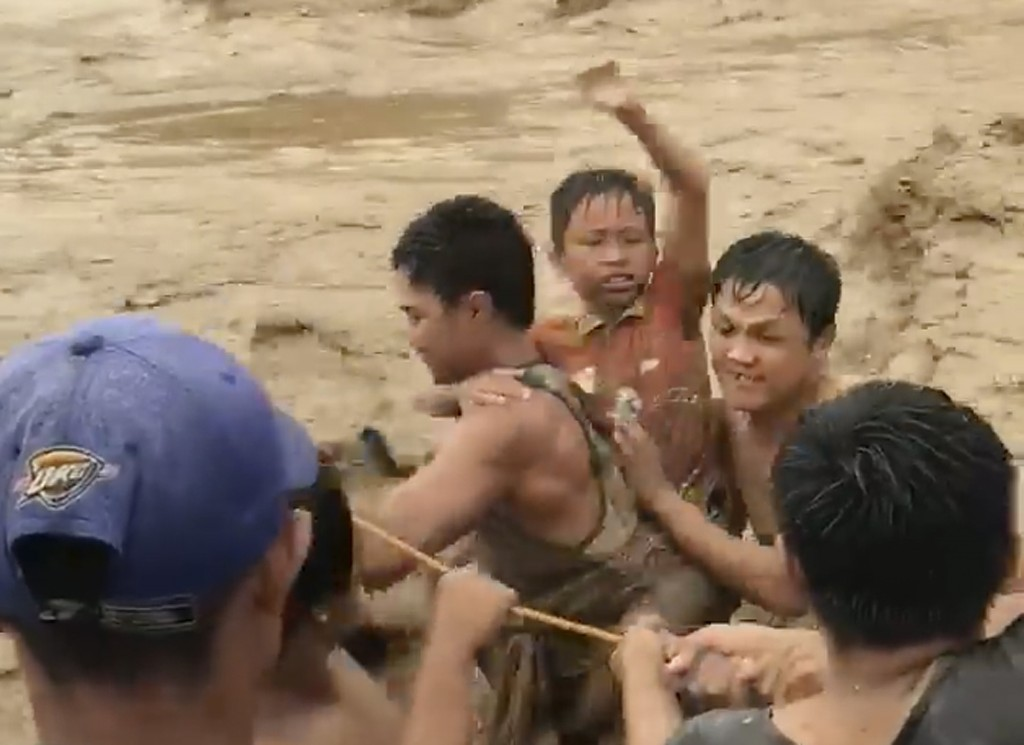 In this photo made from video by Aclimah Disumala, Friday, Dec. 22, 2017, villagers cross raging flood waters in Lanao del Norte, Zamboanga Pennisula,...