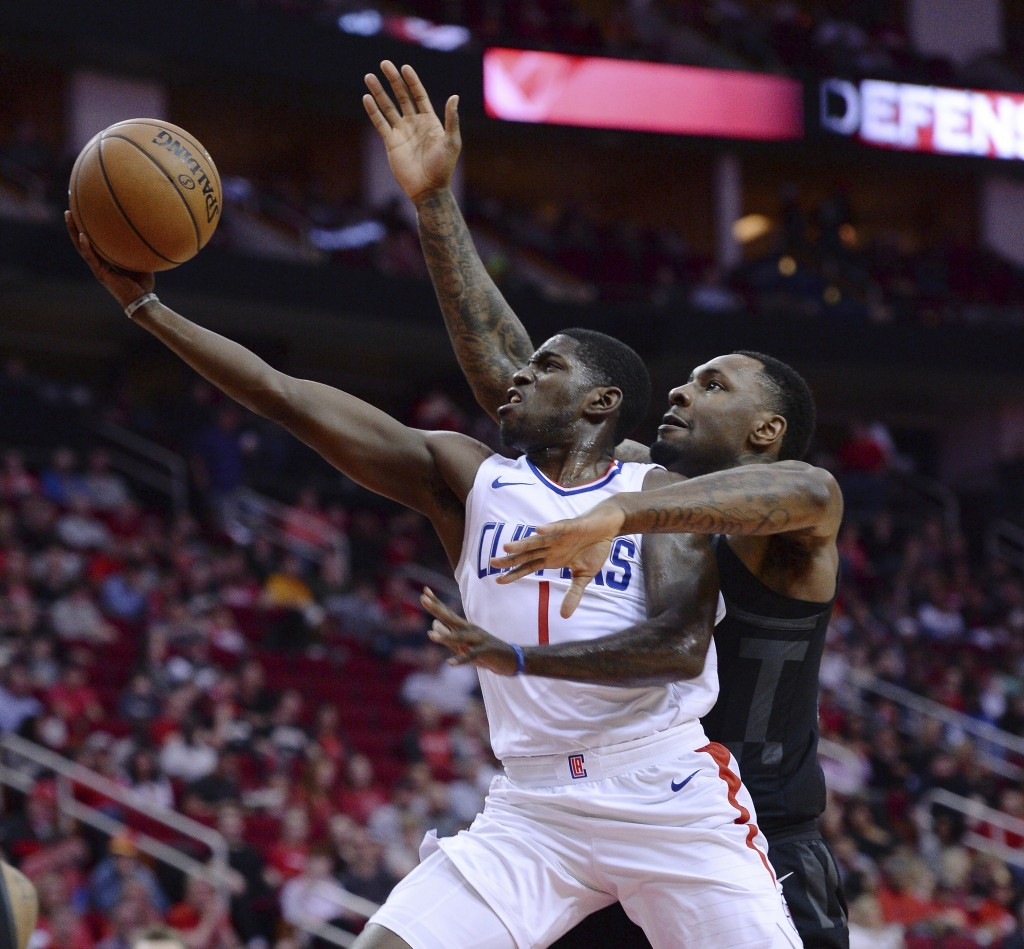 Houston Rockets forward Tarik Black, right, goes up to block the shot of Los Angeles Clippers Jawun Evans (1) during the first half of an NBA basketba...