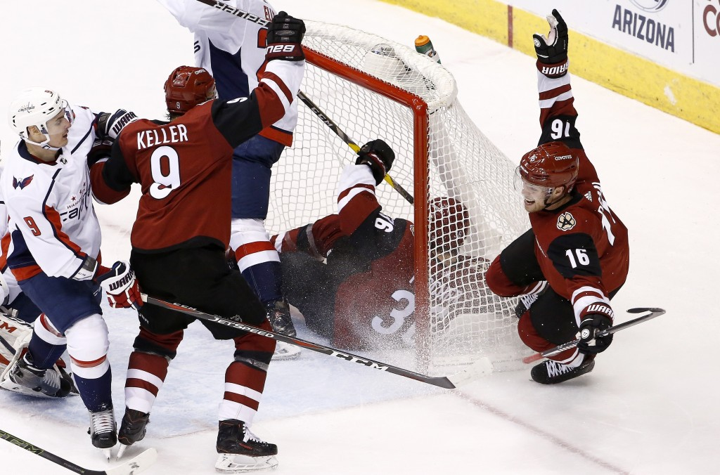 Arizona Coyotes center Clayton Keller (9) and left wing Max Domi (16) celebrate a goal by Coyotes right wing Christian Fischer (36), near Washington C...