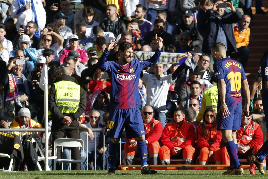 Barcelona's Lionel Messi, left, celebrates after scoring the second goal during a Spanish La Liga soccer match between Real Madrid and Barcelona at th...