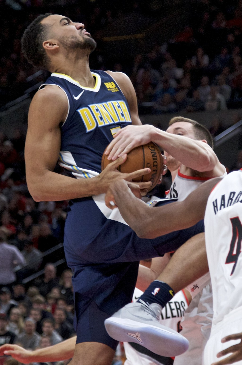 Denver Nuggets forward Trey Lyles, left, is fouled by Portland Trail Blazers guard Pat Connaughton during the first half of an NBA basketball game in ...