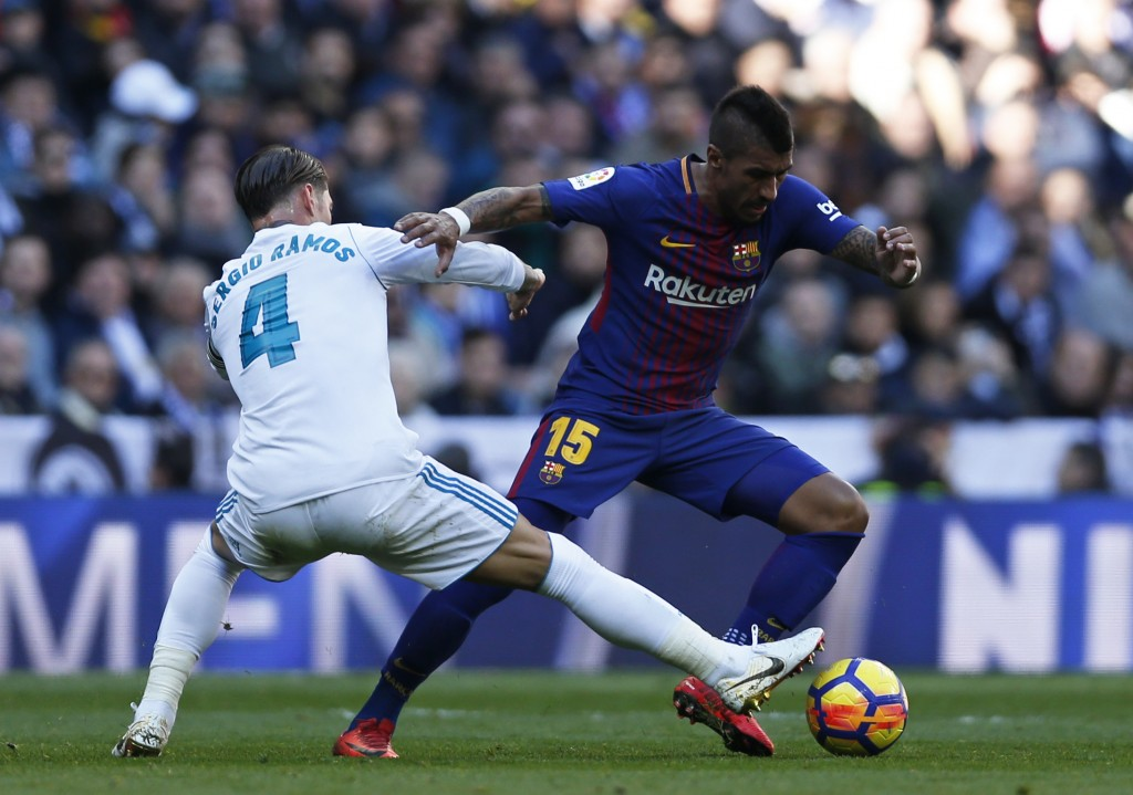 Barcelona's Paulinho fights for the ball with Real Madrid's Sergio Ramos, left, during the Spanish La Liga soccer match between Real Madrid and Barcel...