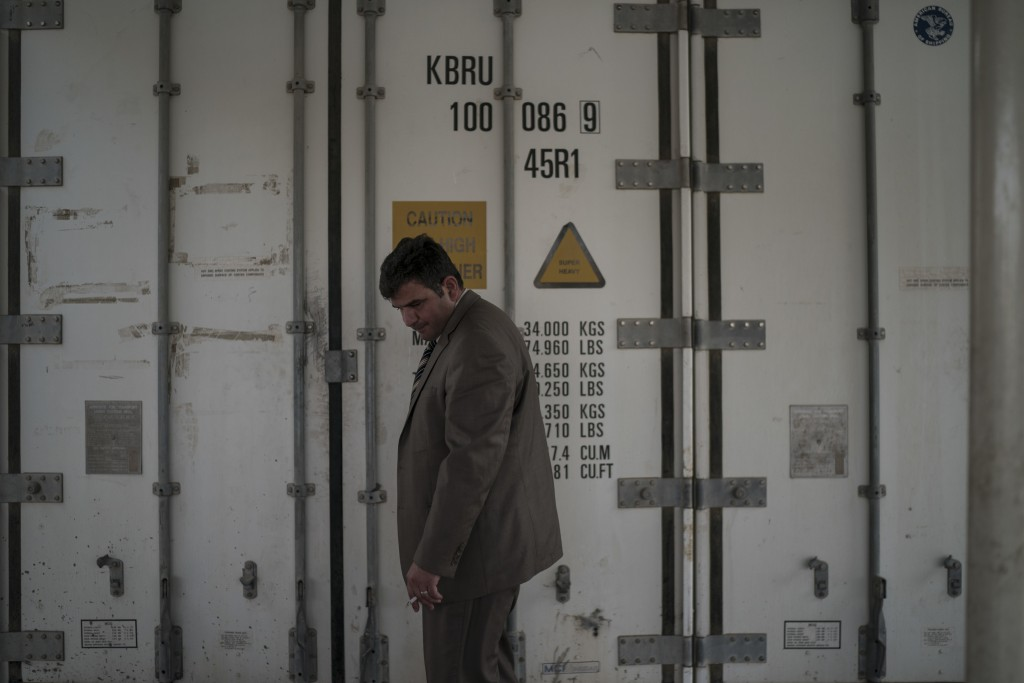 In this Nov. 8, 2017 photo, senior examiner Modhar al-Omari stands outside a refrigerated container carrying dozens of bodies in a morgue in Mosul, Ir...