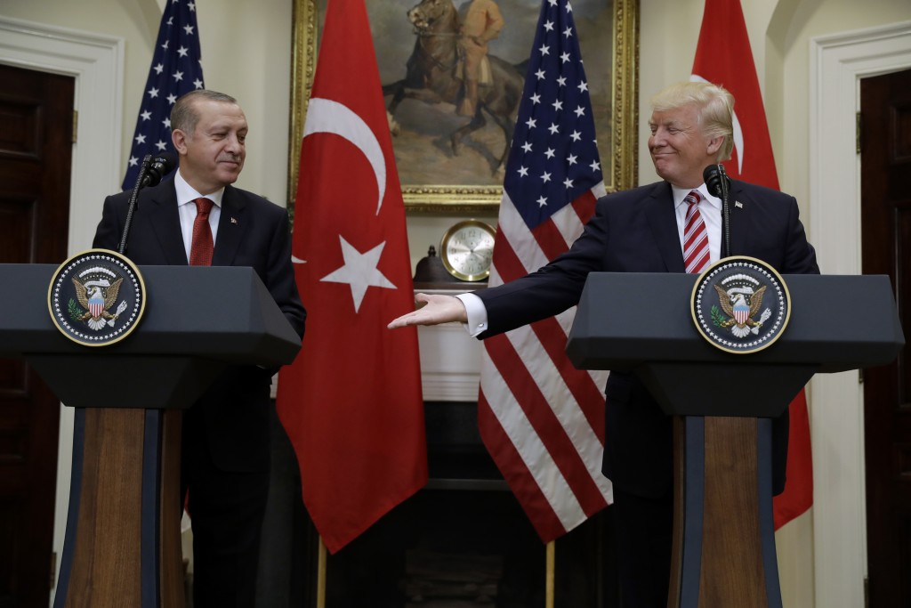 FILE - In this Tuesday, May 16, 2017 file photo, U.S. President Donald Trump, right, reaches to shake hands with Turkey's President Recep Tayyip Erdog...