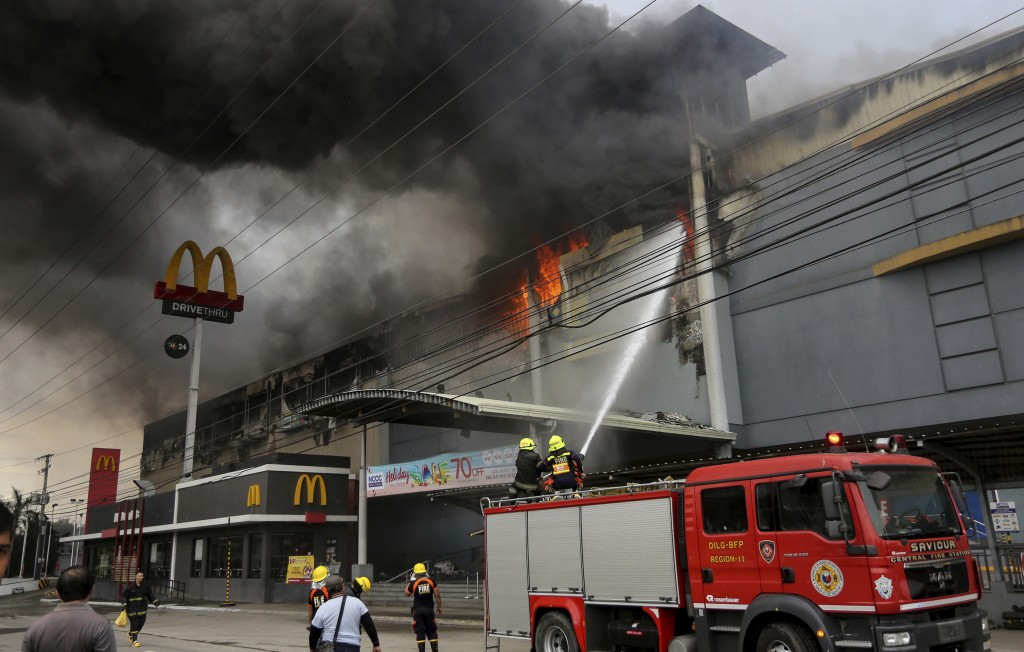 Firemen battle a fire that rages at a shopping mall, Saturday, Dec. 23, 2017, in Davao city, southern Philippines. The fire which still raging for hou...