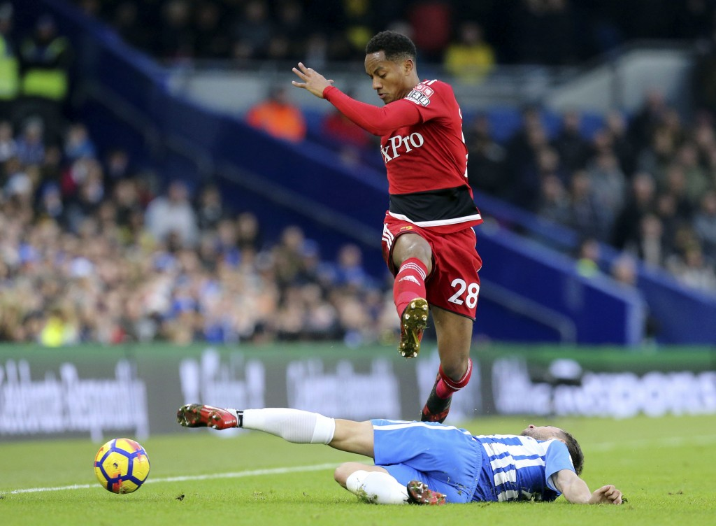 Watford's Andre Carrillo, in air, and Brighton & Hove Albion's Markus Suttner battle for the ball during the English Premier League soccer match betwe...