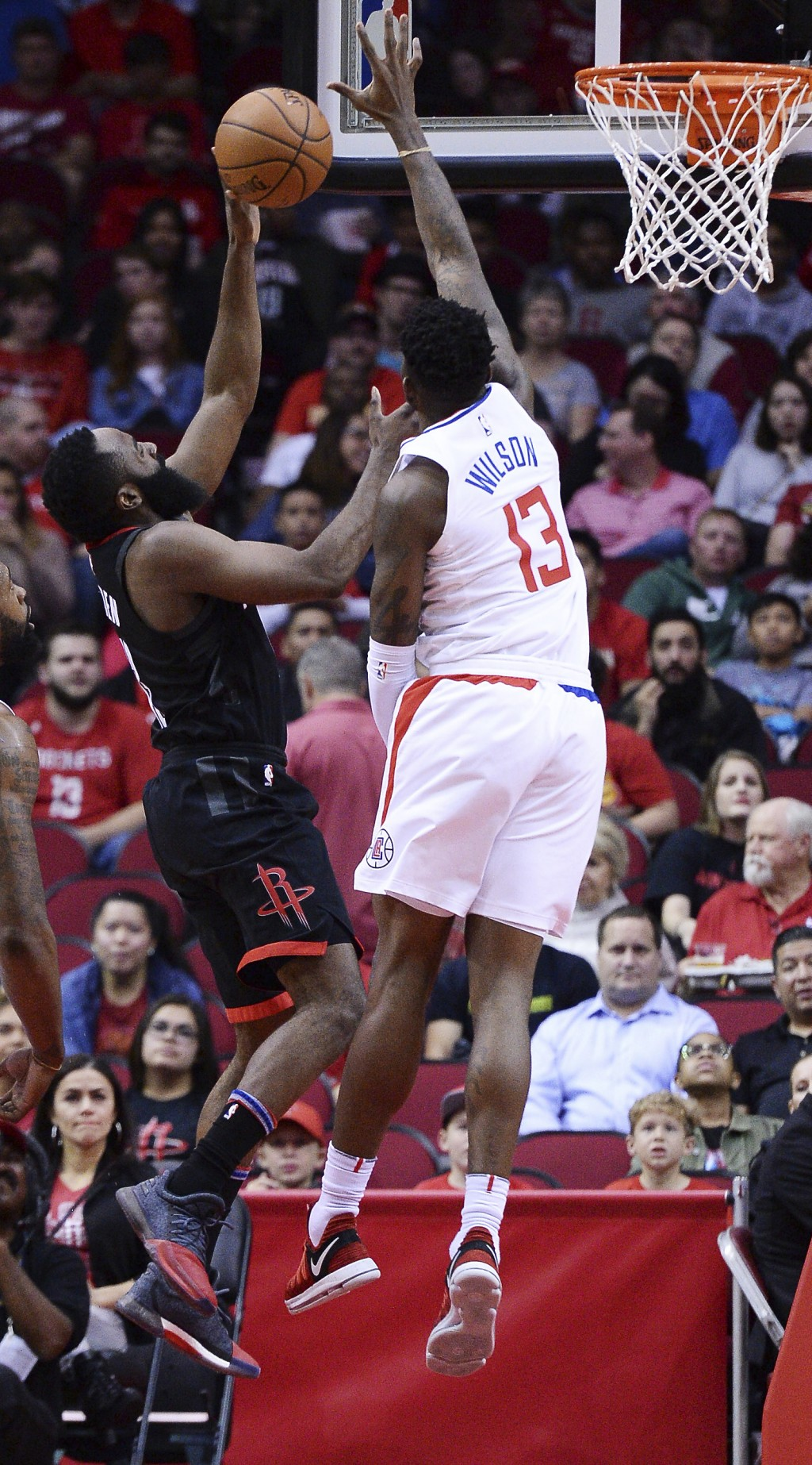 Houston Rockets guard James Harden, left, shoots against Los Angeles Clippers Jamil Wilson during the first half of an NBA basketball game Friday, Dec...