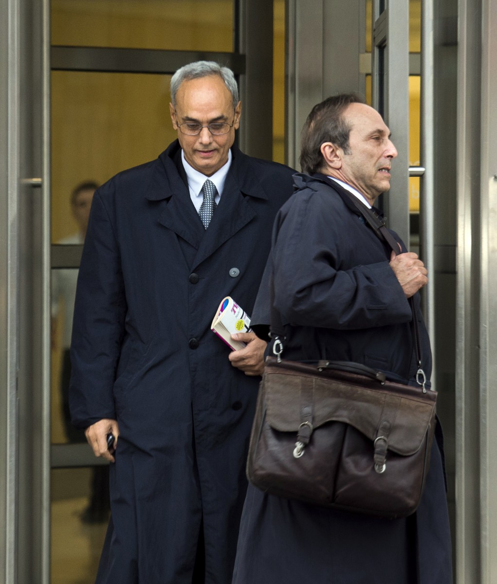 Manuel Burga, left, the former president of Peru's soccer federation, leaves federal court in the Brooklyn borough of New York, Friday, Dec. 22, 2017....