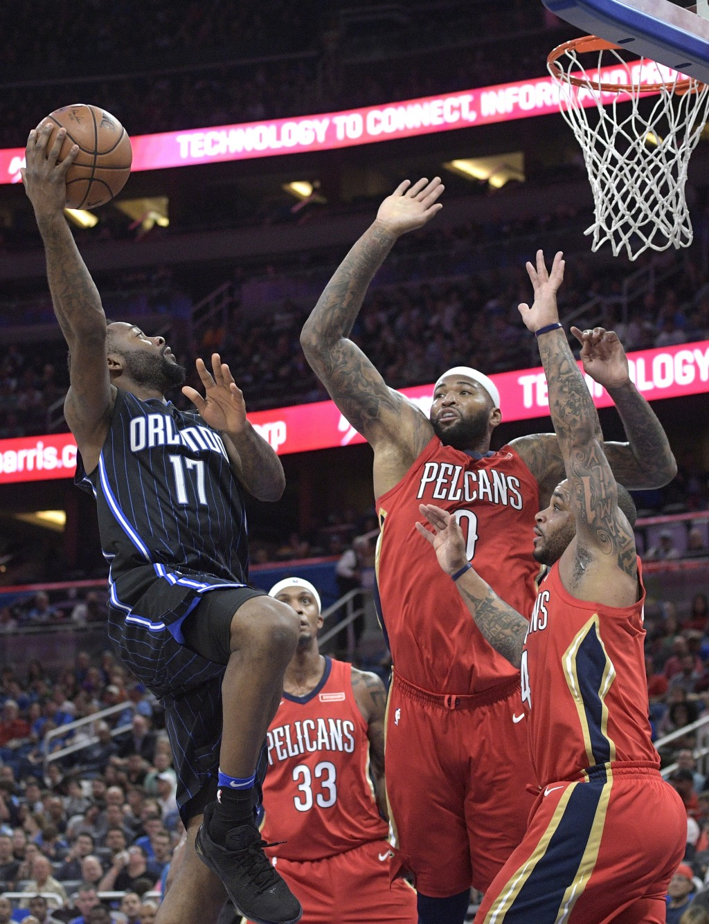 Orlando Magic forward Jonathon Simmons (17) goes up for a shot in front of New Orleans Pelicans forward Dante Cunningham (33), center DeMarcus Cousins...