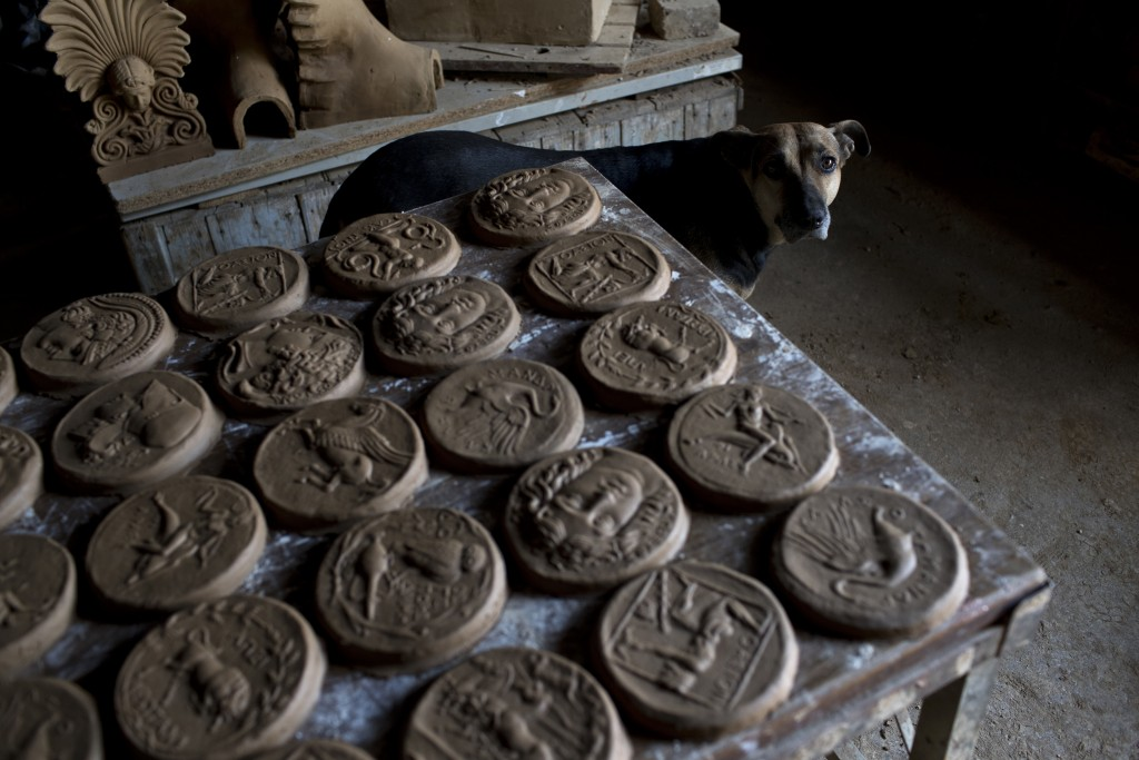 In this Friday, Oct. 13, 2017 photo a dog stands next to ceramic medallions based on ancient Greek coins in Haralambos Goumas' sculpture and ceramic w...