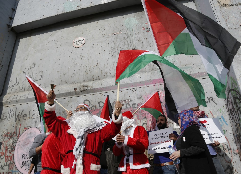 Palestinians dressed as Santa Claus wave national flags in front of the Israeli separation barrier during a protest in the West Bank city of Bethlehem...