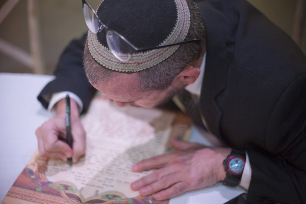 """In this Thursday, Dec. 14, 2017 photo, Rabbi Chuck Davidson signs a"""" Ktuba,"""" a Jewish wedding contract during a wedding in Ein Hemed. A growing number..."""