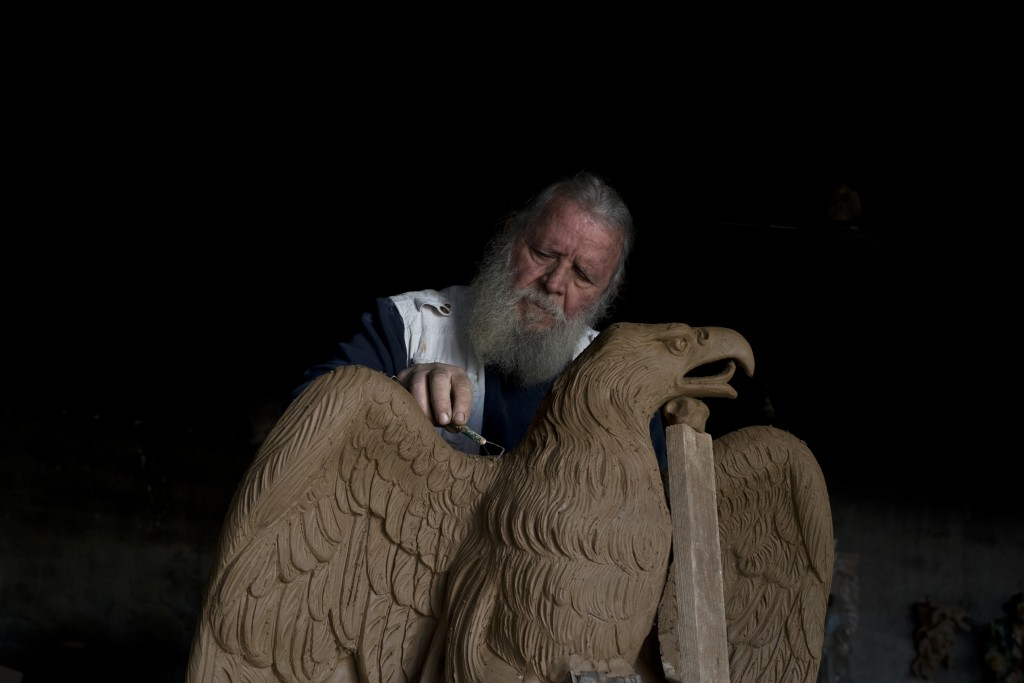 In this Tuesday, Nov. 14, 2017 photo, sculptor and ceramicist Haralambos Goumas works on a terracotta eagle, at his workshop, in the Egaleo suburb of ...