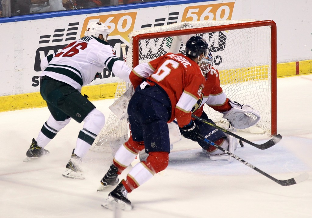 Minnesota Wild's Daniel Winnik, left, scores a goal against Florida Panthers goalie James Reimer as Panthers' Alex Petrovic (6) defends during the sec...