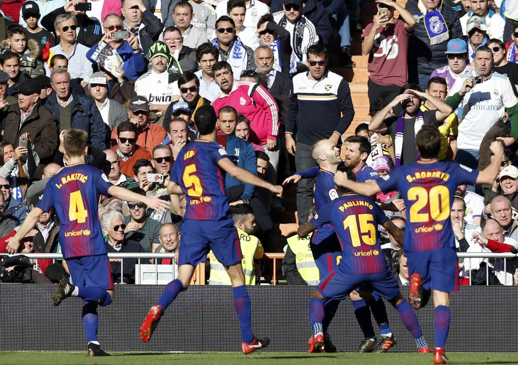 Barcelona's Lionel Messi, 2nd right, celebrates after scoring his side's second goal during the Spanish La Liga soccer match between Real Madrid and B...