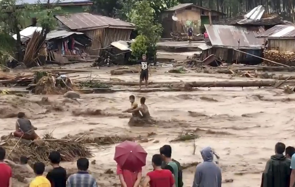 In this photo made from video by Aclimah Disumala, Friday, Dec. 22, 2017, villagers ross raging flood waters in Lanao del Norte, Zamboanga Pennisula, ...