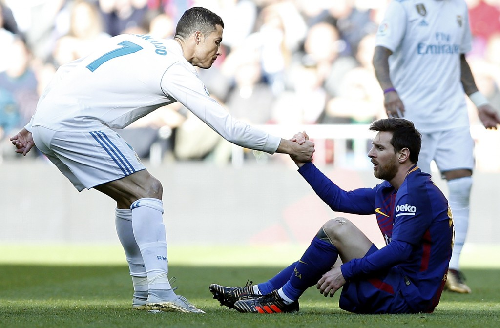 Real Madrid's Cristiano Ronaldo, left, helps Barcelona's Lionel Messi get back on his feet during the Spanish La Liga soccer match between Real Madrid...