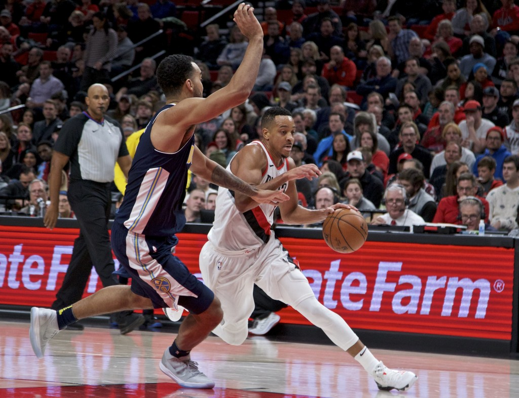 Portland Trail Blazers guard CJ McCollum, right, dribbles past Denver Nuggets forward Trey Lyles during the second half of an NBA basketball game in P...