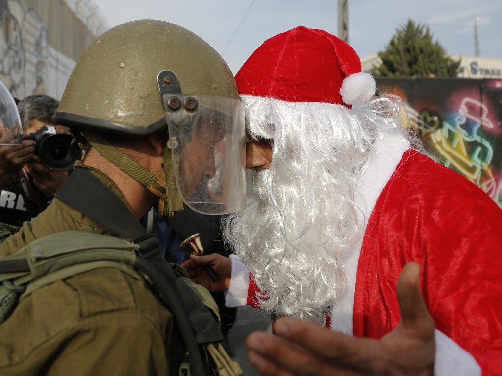 A Palestinian dressed as Santa Claus argues with an Israeli border police during a protest in the West Bank city of Bethlehem, Saturday, Dec. 23, 2017...