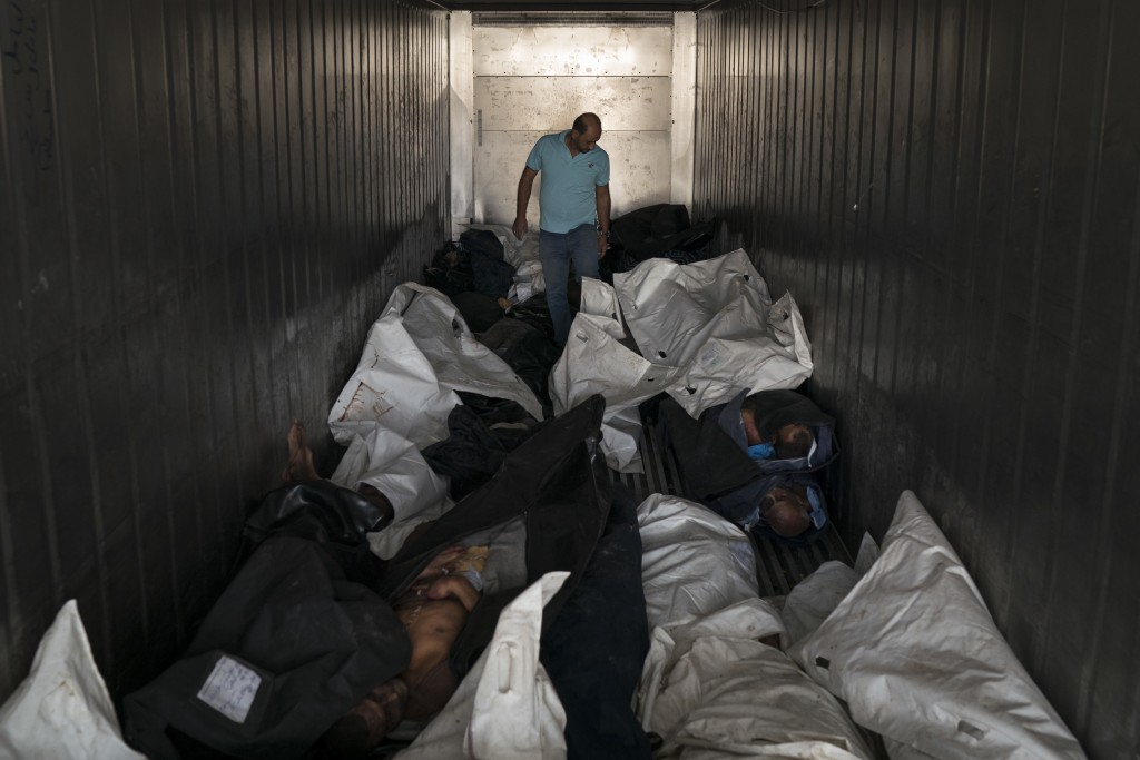 In this Nov. 8, 2017 photo, medical assistant Sameh al-Azzawi walks inside a refrigerated container carrying dozens of bodies in a morgue in Mosul, Ir...