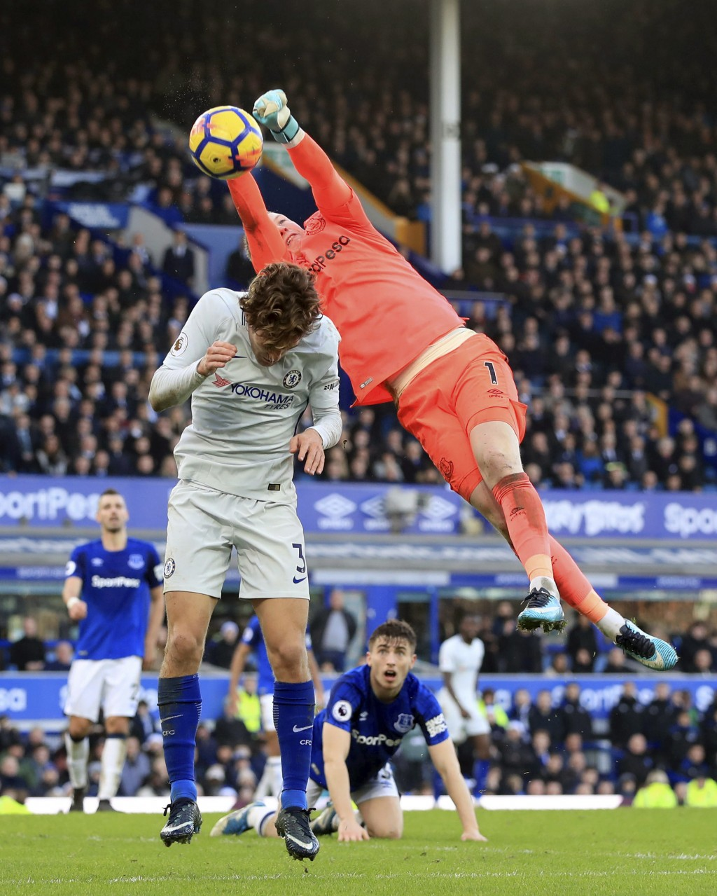 Chelsea's Marcos Alonso, left and Everton goalkeeper Jordan Pickford battle for the ball, during the English Premier League soccer match between Evert...