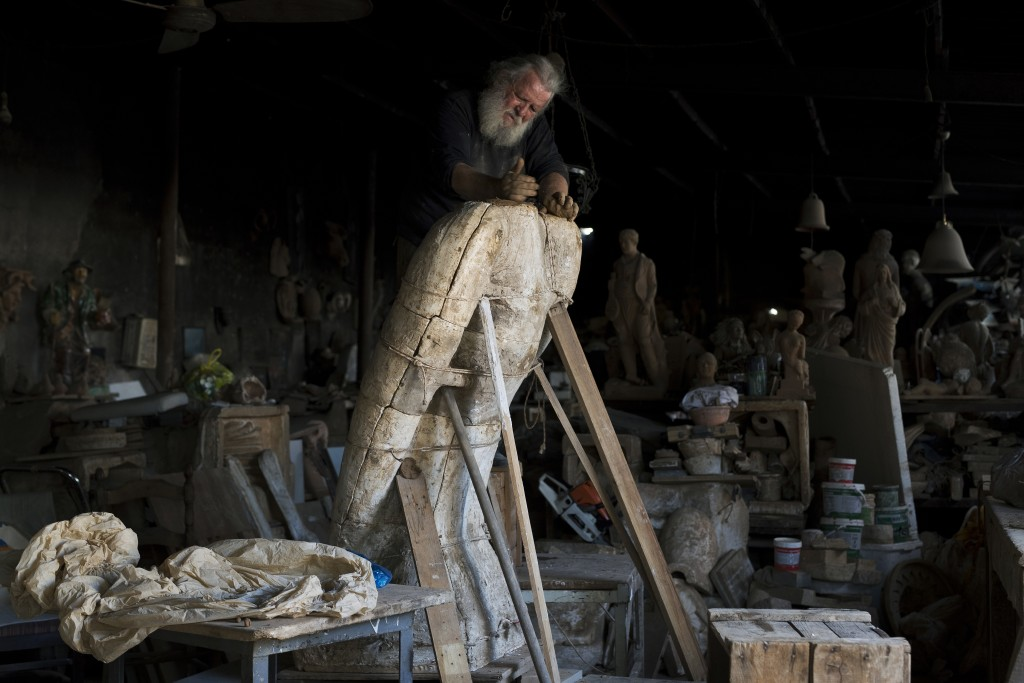In this Thursday, Oct. 19, 2017 photo, sculptor and ceramicist Haralambos Goumas works on a huge terracotta eagle in a mould, at his workshop, in the ...