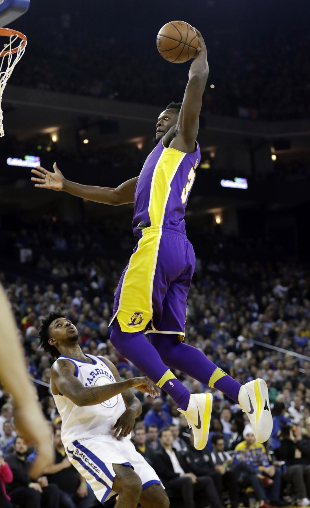 Los Angeles Lakers forward Julius Randle  dunks past Golden State Warriors guard Nick Young during the first half of an NBA basketball game Friday, De...