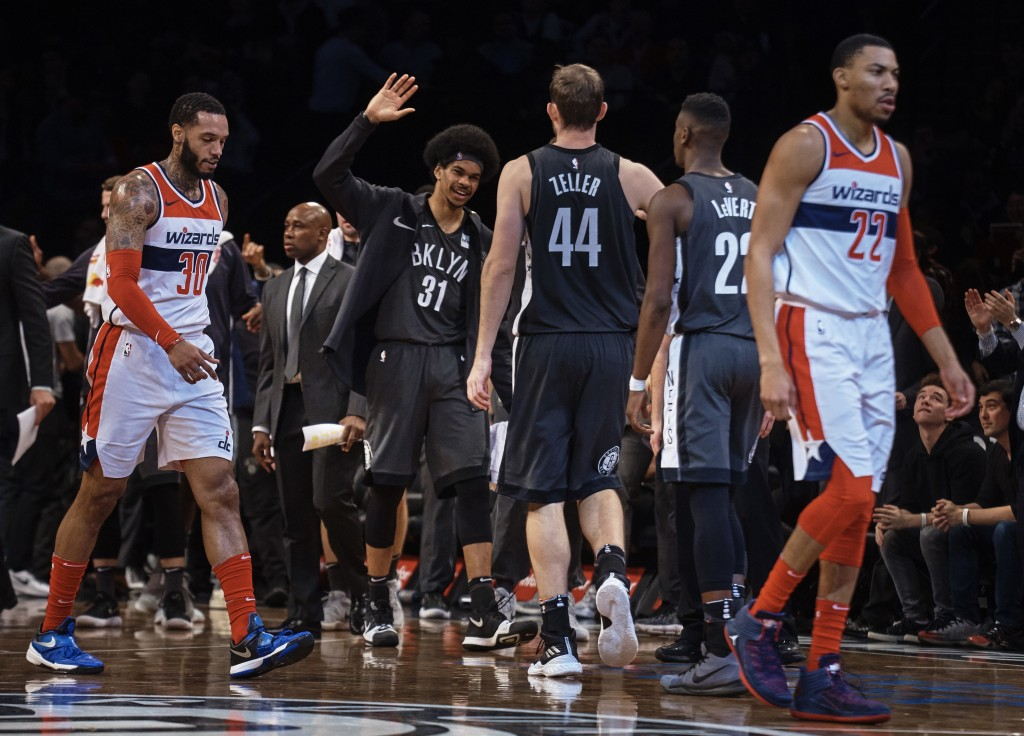 Brooklyn Nets' Jarrett Allen, center left, celebrates with Tyler Zeller (44) during the first half of the team's NBA basketball game against the Washi...