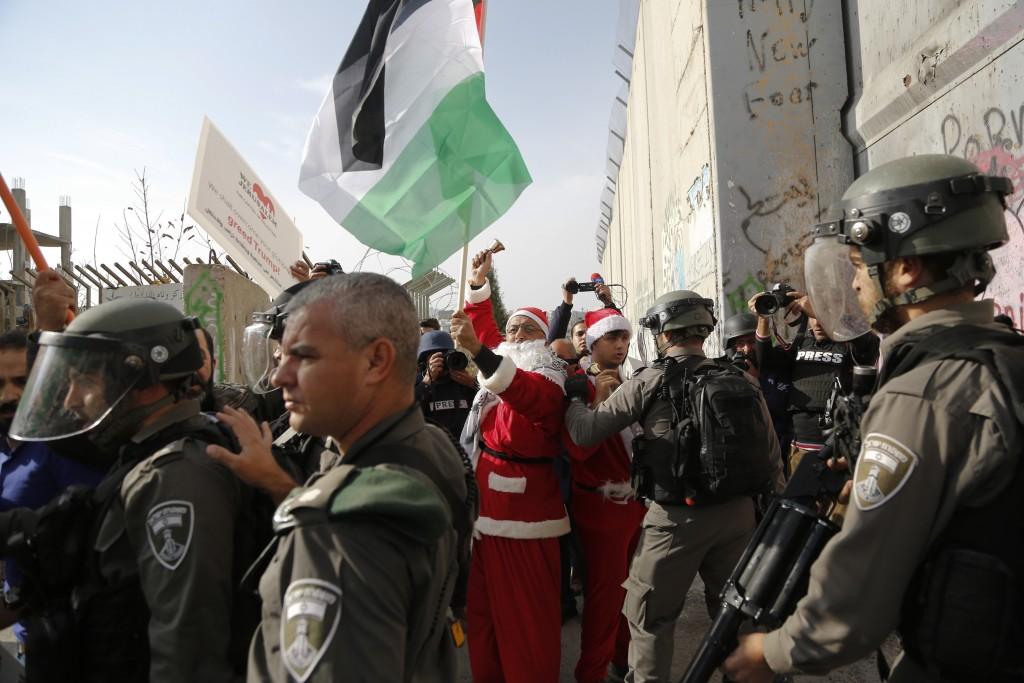 Palestinians dressed as Santa Claus confront Israeli border police during a protest in the West Bank city of Bethlehem, Saturday, Dec. 23, 2017. (AP P...