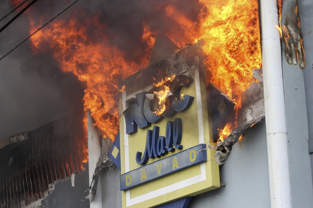 A fire rages on at a shopping mall Saturday, Dec. 23, 2017, Davao city, southern Philippines. As the fire continues to burn, an undetermined number of...