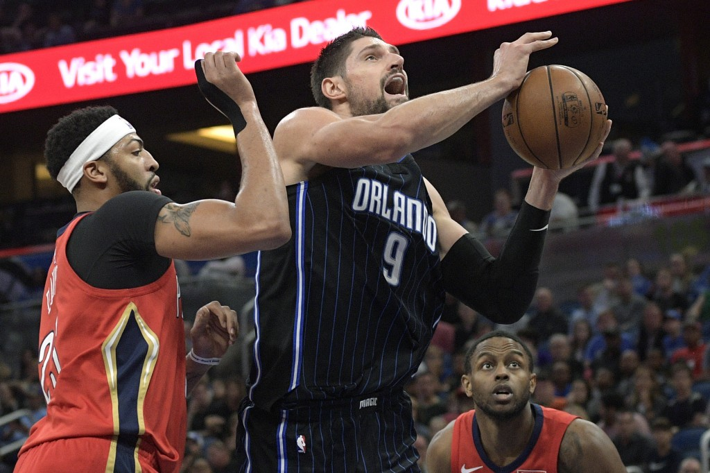 Orlando Magic center Nikola Vucevic (9) goes up for a shot between New Orleans Pelicans forwards Anthony Davis, left, and Darius Miller during the fir...