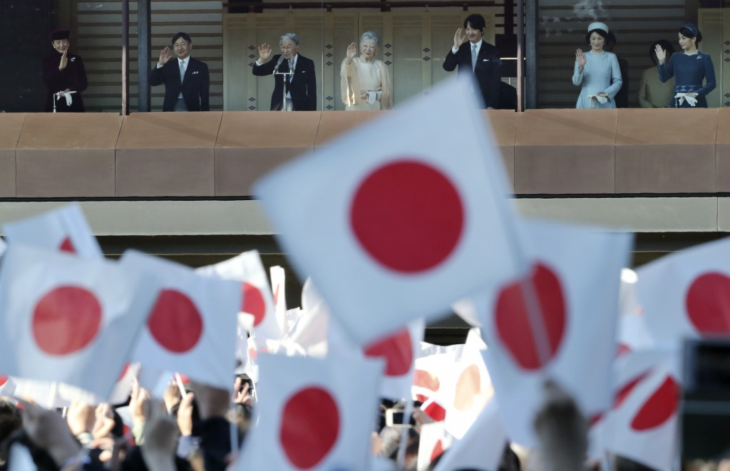 In this Dec. 23, 2017, file photo,  Japan's Emperor Akihito, third from left, waves with his family from a balcony as national flags are waved by well...