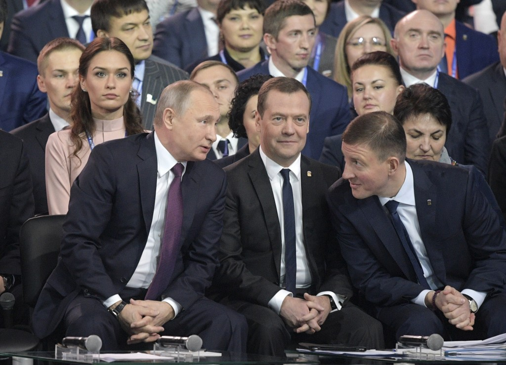Russian President Vladimir Putin, foreground left, speaks to Russian Prime Minister Dmitry Medvedev, center, and acting Secretary of the General Counc...