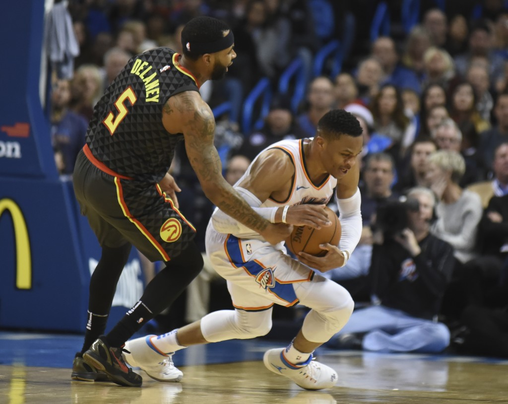 Atlanta Hawks' Malcolm Delaney, left, tries to get the ball away from Oklahoma City Thunder's Russell Westbrook, right, in the third quarter of an NBA...