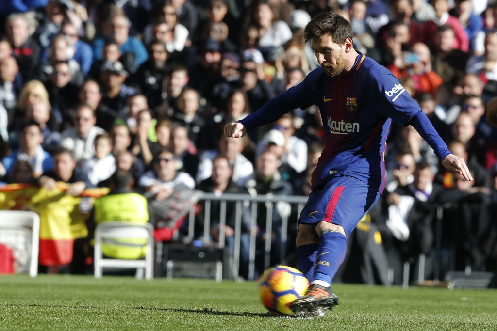 Barcelona's Lionel Messi scores from a penalty kick during a Spanish La Liga soccer match between Real Madrid and Barcelona at the Santiago Bernabeu s...