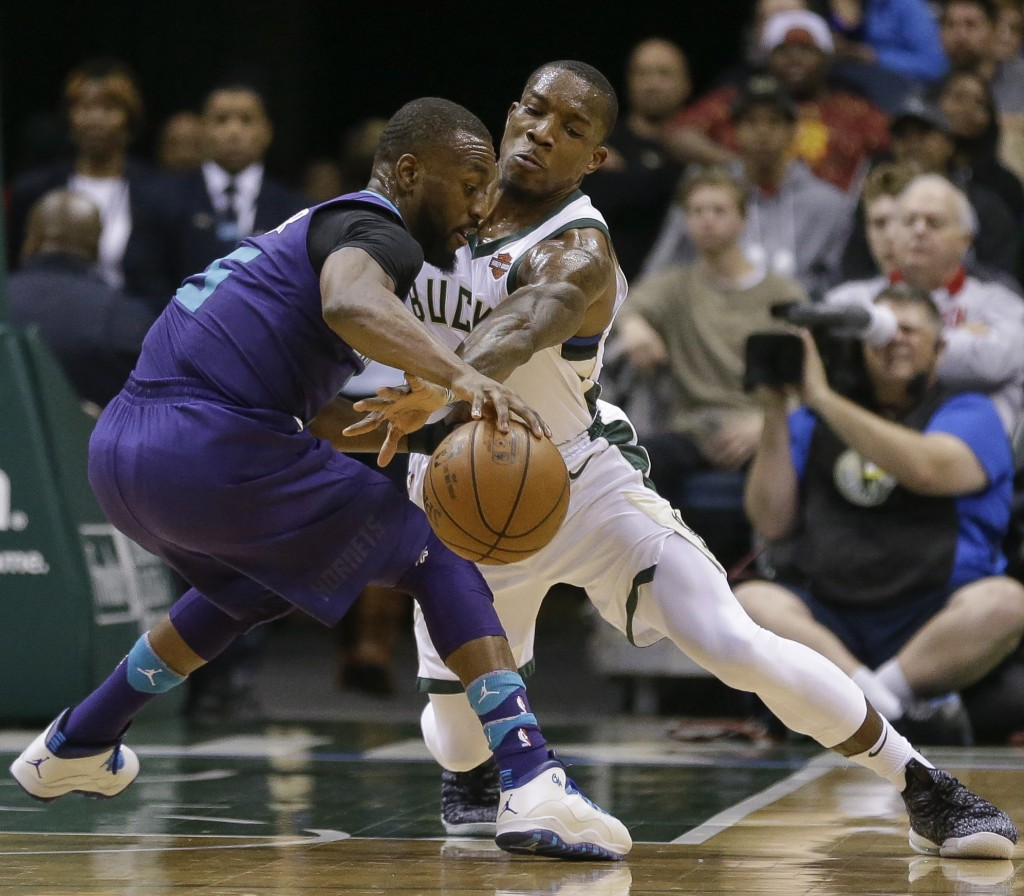 Milwaukee Bucks' Eric Bledsoe makes a steal attempt on Charlotte Hornets' Nicolas Batum, left, during the second half of an NBA basketball game Friday...
