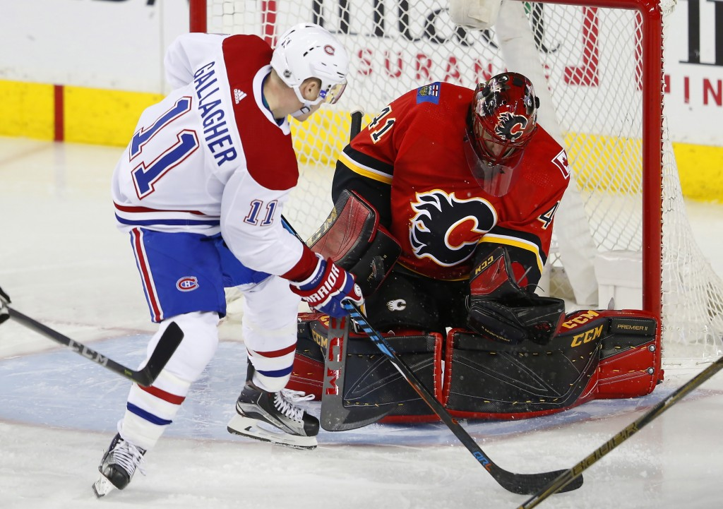 Calgary Flames goalie Mike Smith makes a save on Montreal Canadiens' Brendan Gallagher during the third period of an NHL hockey game Friday, Dec. 22, ...