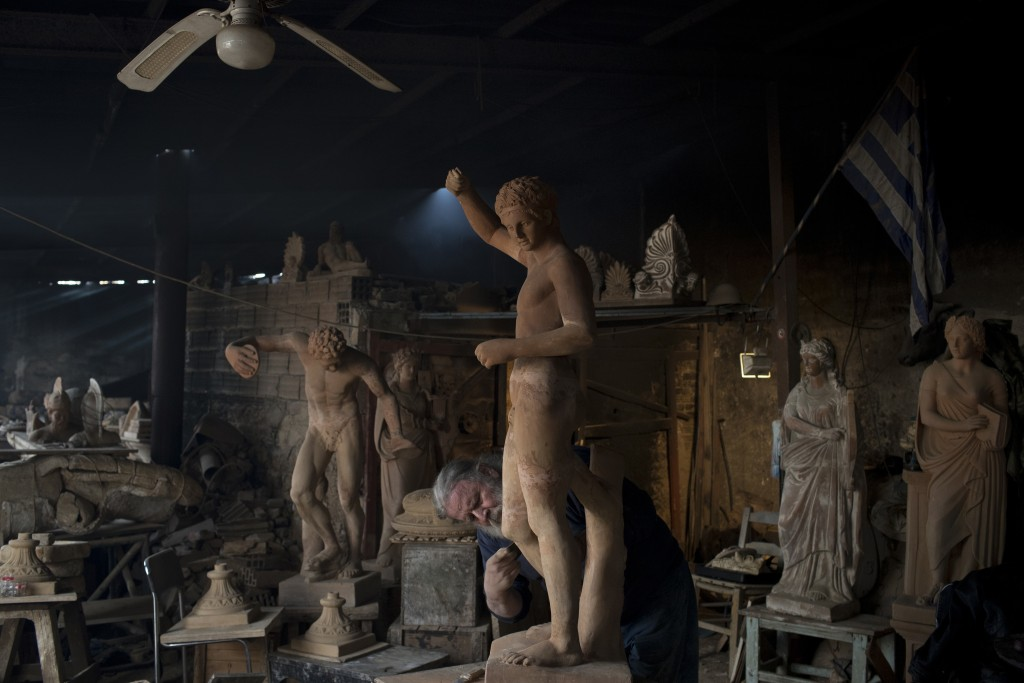 In this Tuesday, Dec. 19, 2017 photo, sculptor and ceramicist Haralambos Goumas works on a terracotta statue of Hermes, messenger of the ancient Greek...