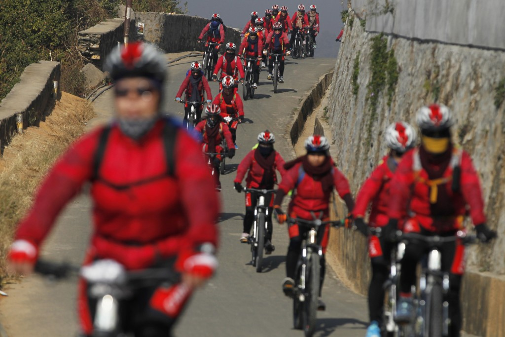 In this Dec. 23, 2017, file photo, Buddhist nuns participate on a month long bicycle pilgrimage in Kathmandu, Nepal. Roughly 200 Drukpa Kung-Fu Nuns b...