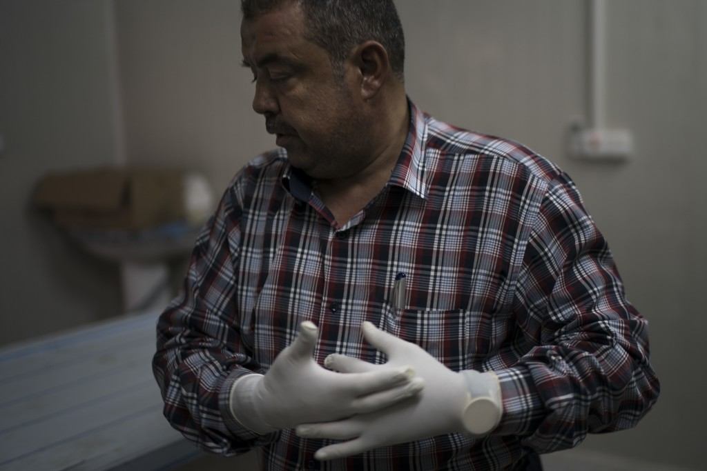 In this Nov. 8, 2017 photo, chief medical assistant Raid Jassim adjusts his gloves before inspecting a body in a morgue in Mosul, Iraq. The morgue sta...